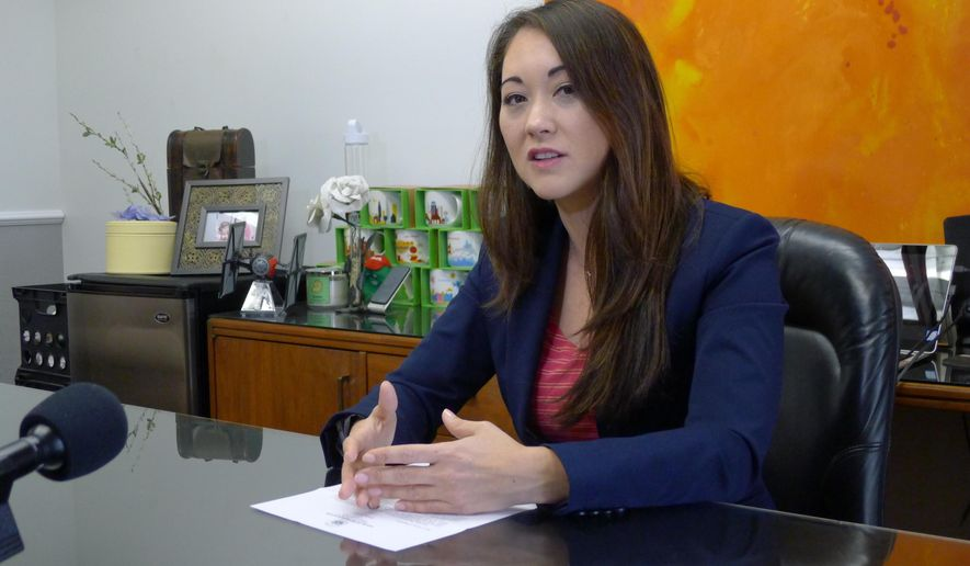 FILE- In this Feb. 1, 2017, file photo, Hawaii Rep. Beth Fukumoto talks with reporters in her capitol office in Honolulu, Hawaii. In deep-blue Hawaii, Fukumoto is considering switching parties to become a Democrat after she was pressured to resign her leadership role for criticizing President Donald Trump. (AP Photo/Cathy Bussewitz, File)