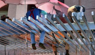 Construction workers try to shade themselves from the direct sun while welding a steel awning on a building in downtown Los Angeles on Monday, June 19, 2017. A heatwave in the southwest and California is creating a public health hazard. (AP Photo/Richard Vogel)