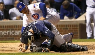 San Diego Padres catcher Austin Hedges stays on the ground after tagging out Chicago Cubs' Anthony Rizzo during a collision at home during the sixth inning of a baseball game Monday, June 19, 2017, in Chicago. (AP Photo/Charles Rex Arbogast)