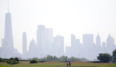 In a photo taken Tuesday, June 13, 2017, in Jersey City, N.J., a golfer and his caddie walk along the fairway on the No. 1 hole with the New York City skyline as a backdrop at Liberty National Golf Club. The club will host the Presidents Cup in late September. (AP Photo/Julio Cortez)