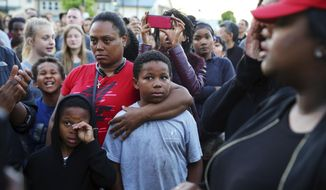 Florida Carroll, wearing red, a step-sister of Charleena Lyles, stands with several dozen people attending a vigil outside the apartment building of Lyles, a 30-year-old woman who was shot by police after she called them to respond to an attempted burglary, Sunday, June 18, 2017. Lyles has a history of mental illness and police say she brandished a knife during the incident. (Genna Martin/seattlepi.com via AP)
