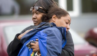 Monika Williams, front, a relative of the victim, is comforted at the scene a police shooting at the Brettler Family Place Apartments at Magnuson Park, Sunday June 18, 2017, in Seattle. According to police, two officers responded to a burglary call made by the woman, who they say brandished a knife at some point, and both officers shot her dead in her apartment. Children were home at the time and were physically unharmed. (Bettina Hansen/The Seattle Times via AP)