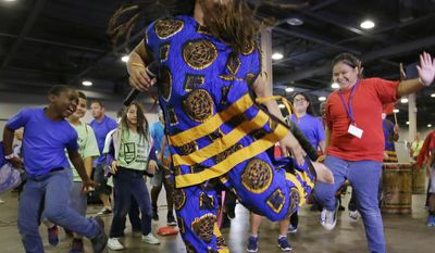 T.J. with the Bandan Koro African Dance Ensemble leads children dancing during a Juneteenth celebration at Fair Park in Dallas, Monday, June 19, 2017. Juneteenth celebrates the end of slavery in Texas. (AP Photo/LM Otero)