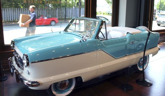 """In this June 13, 2017 photo, a pedestrian walks past a display of a 1959 Nash Convertible """"Metropolitan"""" at the Audrain Automobile Museum in Newport, R.I. (AP Photo/Michelle R. Smith)"""