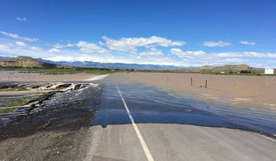 This Monday, June 19, 2017 photo provided by the Wyoming Department of Transportation shows water from the flooded Wind River in Fremont County flowing over Highway U.S. 26 in Kinnear, Wyo. The highway was closed to traffic in both directions. Several small state highways nearby were also closed because of the high water. Rain over the weekend caused flooding along rivers and streams already running high from mountain snowmelt. (Wyoming Department of Transportation)