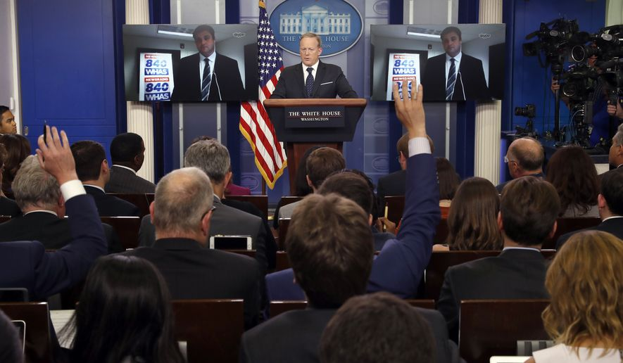 White House press secretary Sean Spicer answers a question from Will Clark, from WHAS, who is seen on the video screens, during a briefing at the White House, Tuesday, June 20, 2017 in Washington. (AP Photo/Alex Brandon)