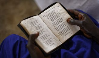 In this photo taken Sunday, June 4, 2017, a woman church leader reads from a bible in her native Bari language, at the United Church which is held in a school classroom tent, in Bidi Bidi refugee settlement in northern Uganda. The South Sudanese refugees meet in open-air churches rigged from timber with seats made only from planks of wood or logs drilled into the ground, yet these churches for the born-again Christians are oases of joy among the daily humiliations that come with rebuilding their lives. (AP Photo/Ben Curtis)