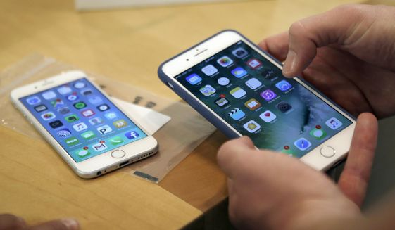 In this Friday, Sept. 16, 2016, file photo, a customer sets up his new iPhone 7 Plus, right, as he switches from the iPhone 6 at the Apple Store on Michigan Avenue during the release of the Apple iPhone 7 and the latest Apple Watches, in Chicago. (AP Photo/Kiichiro Sato, File)