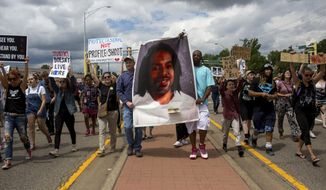 Protesters hold an image Philando Castile and march down the street during a protest, Sunday, June 18, 2017, in St. Anthony, Minn.  The protesters marched against the acquittal of Officer Jeronimo Yanez, was found not guilty of manslaughter for shooting Castile during a traffic stop. (Courtney Pedroza/Star Tribune via AP)