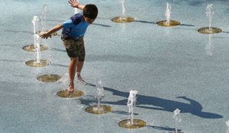 One person uses the CityScape splash pad to stay cool as temperatures climb to near-record highs Tuesday, June 20, 2017, in Phoenix. The National Weather Service forecasts a high of 120 degrees (49 degrees Celsius), which is has only hit three times in recorded history in Phoenix, the last time 22 years ago. (AP Photo/Ross D. Franklin)