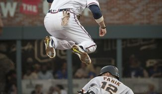 Atlanta Braves shortstop Dansby Swanson (7) watches his throw to first after forcing out San Francisco Giants' Joe Panik (12) during the first inning of a baseball game, Tuesday, June 20, 2017, in Atlanta. Brandon Crawford was out at first. (AP Photo/John Amis)
