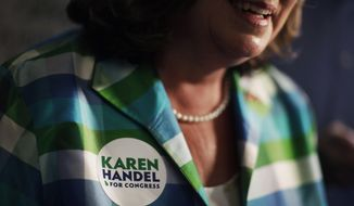 A sticker decorates the shirt of Karen Handel, Republican candidate for Georgia's 6th congressional district as she talks to reporters during a campaign stop at Old Hickory House in Tucker, Ga., Monday, June 19, 2017. The race between Handel and Democrat Jon Ossoff is seen as a significant political test for the new Trump Administration. The district traditionally goes Republican, but most consider the race too close to call as voters head to the polls on Tuesday. (AP Photo/David Goldman)