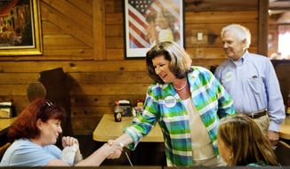Karen Handel, Republican candidate for Georgia's 6th Congressional District, center, greets diners during a campaign stop at Old Hickory House in Tucker, Ga., Monday, June 19, 2017. The race between Handel and Democrat Jon Ossoff is seen as a significant political test for the new Trump Administration. The district traditionally goes Republican, but most consider the race too close to call as voters head to the polls on Tuesday. (AP Photo/David Goldman)