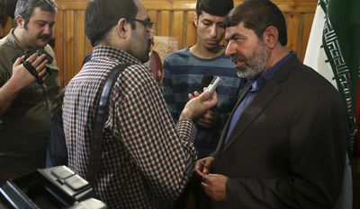 "The spokesman of Iran's Revolutionary Guard, Gen. Ramazan Sharif, right, speaks with media members at the conclusion of his press conference in Tehran, Iran, Tuesday, June 20, 2017. Sharif, said all six ballistic missiles it launched on Syria hit their targets, according to ""local sources and drone films."" Iran fired ballistic missiles at IS targets in eastern Syria, in the province of Deir el-Zour, later on Sunday. (AP Photo/Vahid Salemi)"