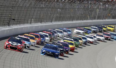 Kyle Larson, left, and Martin Truex Jr. lead the field to start the NASCAR Sprint Cup series auto race, Sunday, June 18, 2017, in Brooklyn, Mich. (AP Photo/Carlos Osorio)