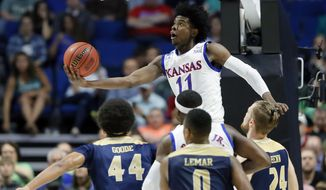 FILE - In this March 17, 2017, file photo, Kansas's Josh Jackson (11) goes up for a shot over UC Davis's Garrison Goode (44), Brynton Lemar (0) and Mikey Henn (24) in the first half of a first-round game in the men's NCAA college basketball tournament in Tulsa, Okla. Jackson spent one season at Kansas and is expected to be a top-five pick in Thursday's NBA draft. (AP Photo/Tony Gutierrez, File)