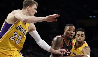 FILE - In this Oct. 11, 2016, file photo, Portland Trail Blazers guard Damian Lillard, center, drives between Los Angeles Lakers center Timofey Mozgov (20) and guard D'Angelo Russell, right, during the first half of an NBA preseason basketball game in Los Angeles. Three people with knowledge of the deal say the Lakers have agreed to trade Russell and Mozgov to the Brooklyn Nets for big man Brook Lopez and the 27th overall pick in the upcoming draft. The people spoke to The Associated Press on condition of anonymity because the trade hadn't been consummated Tuesday, June 20, 2017. (AP Photo/Alex Gallardo, File)
