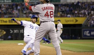 Kansas City Royals Drew Butera, left, slides into third base with a triple as Boston Red Sox third baseman Pablo Sandoval, right, waits for the throw in the seventh inning of a baseball game at Kauffman Stadium in Kansas City, Mo., Monday, June 19, 2017. (AP Photo/Colin E. Braley)