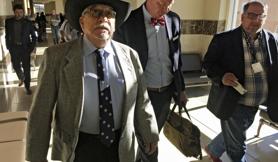 FILE- In this April 4, 2016, file photo, former New Mexico state Sen. Phil Griego, left, and his attorney Tom Clark, center, walk out of an arraignment in Santa Fe District Court in Santa Fe, N.M. A grand jury has charged Griego with perjury, fraud and embezzlement in connection with campaign finance activities, as the prominent Democrat awaits trial in a corruption probe.  (AP Photo/Morgan Lee, file)