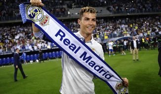 FILE - In this Sunday, May 21, 2017 file photo, Real Madrid's Cristiano Ronaldo celebrates after winning a Spanish La Liga soccer match between Malaga and Real Madrid in Malaga, Spain.A Spanish judge has summoned Real Madrid forward Cristiano Ronaldo to court to answer questions after he was accused of tax fraud by a state prosecutor. (AP Photo/Daniel Tejedor, File)