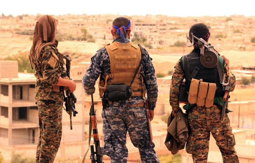 FILE - This April 30, 2017 file photo, provided by the Syrian Democratic Forces (SDF), shows fighters from the SDF looking toward the northern town of Tabqa, Syria. Syrian government and allied troops have inserted themselves into the battle against Islamic State militants by capturing key areas on the flanks of the coalition-led battle to seize Raqqa. They have positioned themselves as indispensable possibly spoilers in the fight to uproot the militants from Syria. (Syrian Democratic Forces, via AP, File)
