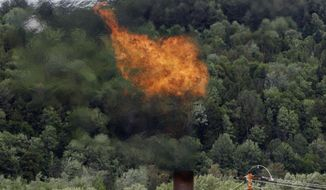 In this June 15, 2005, file photo, flames from methane burning at the landfill in Coventry, Vt. The Trump administration is delaying two Obama-era regulations aimed at restricting harmful methane emissions from oil and gas production. (AP Photo/Toby Talbot, File)