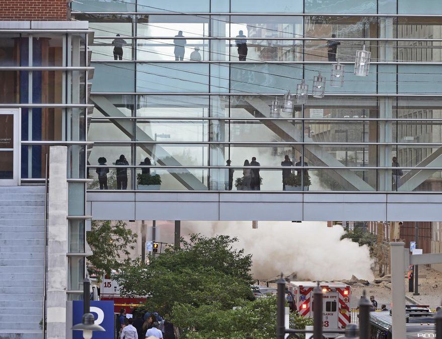 Steam rises after a steam pipe explosion on Tuesday, June 20, 2017, in Baltimore, Md. The underground steam pipe explosion rocked downtown Baltimore Tuesday afternoon, buckling the street, shattering windows on cars and buildings, and gushing a steam plume several stories high for more than an hour. (Kenneth K. Lam/The Baltimore Sun via AP)