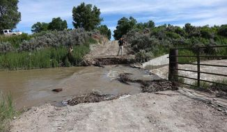 In this Monday, June 19, 2017 photo Fremont County undersheriff Ryan Lee inspects a bridge that was destroyed by flooding outside of Riverton, Wyo. Flooding has damaged some rural roads in Fremont County but all major highways, including U.S. 26, reopened by Tuesday. (Daniel Bendsten /The Ranger via AP)