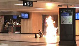 """In this June 20, 2017, photo, a man blows up an explosive device in the station in Brussels. The man was shot by soldiers afterwards in what prosecutors are treating as a """"terrorist attack."""" He lay still for several hours while a bomb squad checked whether he was carrying more explosives and later died. No one else was hurt. (Remy Bonnaffe via AP)"""