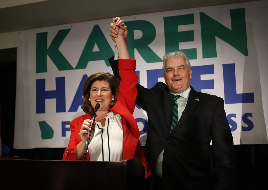 Karen Handel, Republican candidate for Georgia's 6th District Congressional seat, celebrates with her husband Steve as she declares victory during an election-night watch party in Atlanta on Tuesday, June 20, 2017. (Associated Press)
