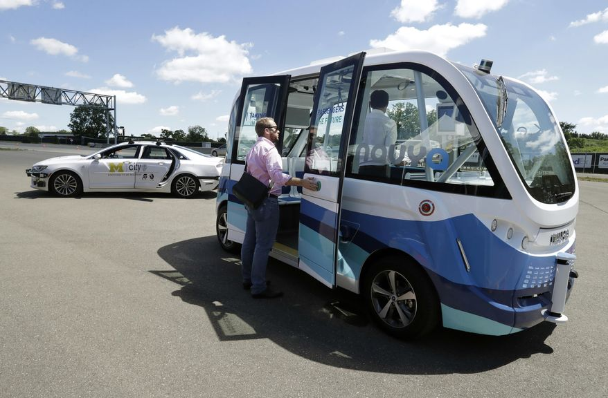 A driverless shuttle is shown parked at the University of Michigan, Wednesday, June 21, 2017, in Ann Arbor, Mich. Two driverless shuttles will begin operating at the university this fall. The tall, airy, 15-passenger shuttles will carry students and staff in a two-mile loop on campus roads alongside regular traffic. The shuttle will be free and insured by the university. The electric shuttles are made by French startup NAVYA, which has deployed 25 shuttles worldwide since last year and is operating them on campuses in Australia and Japan. (AP Photo/Carlos Osorio)