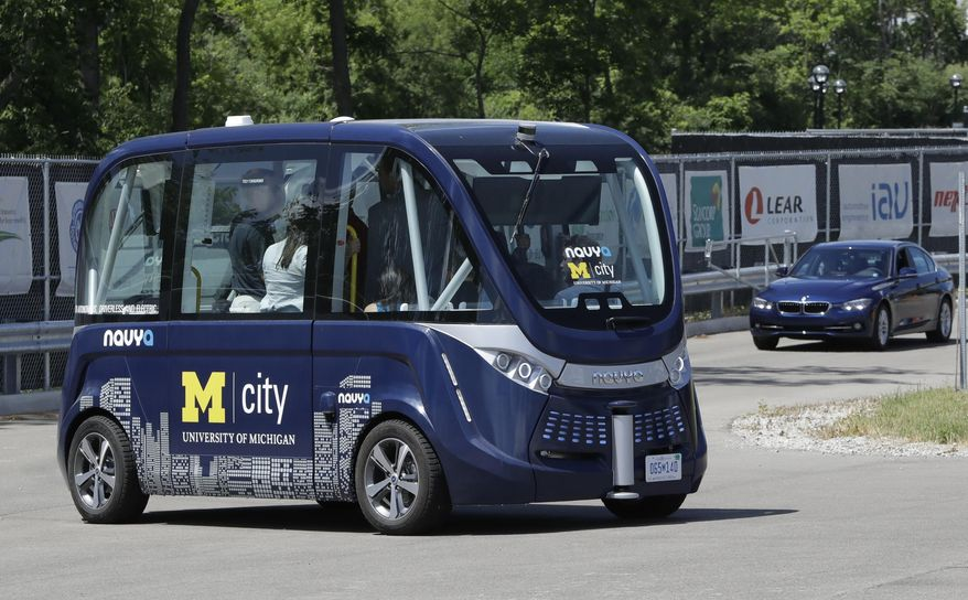 A driverless shuttle carries passengers at the University of Michigan, Wednesday, June 21, 2017, in Ann Arbor, Mich. Two driverless shuttles will begin operating at the university this fall. The tall, airy, 15-passenger shuttles will carry students and staff in a two-mile loop on campus roads alongside regular traffic. The shuttle will be free and insured by the university. The electric shuttles are made by French startup NAVYA, which has deployed 25 shuttles worldwide since last year and is operating them on campuses in Australia and Japan. (AP Photo/Carlos Osorio)