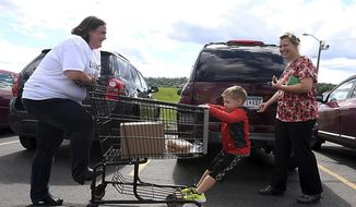 ADVANCE FOR MONDAY JUNE 26 AND THEREAFTER - Volunteer Angie Marble helps Lindsey Lueck and her son Dominic load food into their truck after shopping at Fare for All at New Creation World Outreach Church in Mankato, Minn. The reduced price grocery service swings through the church each month, giving cost-conscious consumers another option for stocking up on fresh veggies and select meats. (Pat Christman/The Free Press via AP)