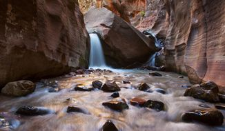 ADVANCE FOR WEEKEND EDITIONS - This June 6, 2017, photo shows the Kanarraville Falls on the outskirts of Kanarraville, Ore. For years, Kanarraville Falls was one of Southern Utah's best-kept secrets. The hidden hike leading to a slot canyon waterfall was seemingly reserved for residents of the small town of Kanarraville. Over the span of a few years, the natural wonder turned into a big problem for the locals. (Jordan Allred/The Spectrum via AP)