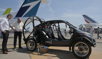 Visitors looks at the flying car Pegasus 1, built by French entrepreneur Jerome Dauffy at Paris Air Show, in Le Bourget, east of Paris, France, Tuesday, June 20, 2017 in Paris. Aviation professionals and spectators are expected at this week's Paris Air Show, coming in, in a thousands from around the world to make business deals. (AP Photo/Michel Euler)