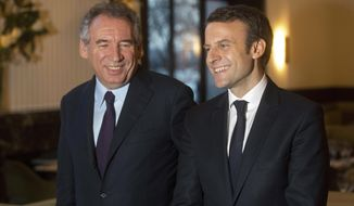 FILE - In this Feb. 23, 2017 file picture, French centrist politician Francois Bayrou, left, and candidate for the 2017 French presidential election, Emmanuel Macron, pose for photographers after a meeting, in Paris, Thursday, Feb. 23, 2017. France's justice minister, Francois Bayrou, who was preparing a draft law to clean up politics but whose party is targeted for possible investigation, resigned on Wednesday to avoid compromising the new government of President Emmanuel Macron, according to French media. (AP Photo/Thibault Camus, File)