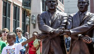 """Spectators hold hands and sing, """"We Shall Overcome,"""" after the unveiling of a sculpture depicting the Rev. Theodore M. Hesburgh holding hands with the Rev. Martin Luther King Jr., Wednesday, June 21, 2017, in South Bend, Ind. The sculpture is based on a famous photo of them participating in a civil rights march in Chicago in 1964,  (Becky Malewitz /South Bend Tribune via AP)"""