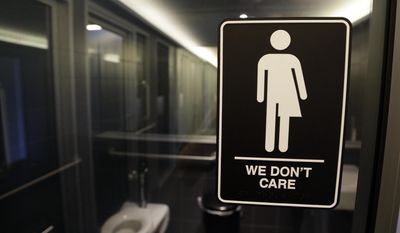 In this Thursday, May 12, 2016 file photo, signage is seen outside a restroom at the 21c Museum Hotel in Durham, N.C. In North Carolina, PayPal and Deutsche Bank cancelled expansion plans and other companies reconsidered their investments in the state after it implemented a measure regarding transgender people, similar to what Montana is considering placing on their 2018 fall ballot. (AP Photo/Gerry Broome, File)