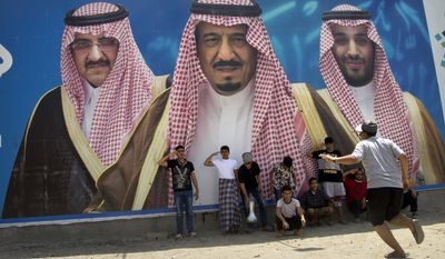 FILE - In this April 4, 2017, file picture Saudi boys pose in front of a huge billboard showing in the center, King Salman, with his 31-year-old son Mohammed bin Salman to the right, and Prince Mohammed bin Nayef to the left in Taif, Saudi Arabia. Salman appointed his son, who was until now the deputy crown prince and country's defense minister, as his successor and first in line to the throne. Salman stripped Mohammed bin Nayef of the title of crown prince and ousted him from his powerful position of interior minister. (AP Photo/Amr Nabil)