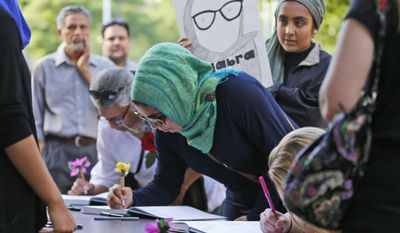 Supporters of Nabra Hassanen, who was killed over the weekend in a road rage incident, sign a condolence book prior to the start of a vigil in honor of Nabar on Wednesday, June 21, 2017, in Reston, Va. (AP Photo/Steve Helber)