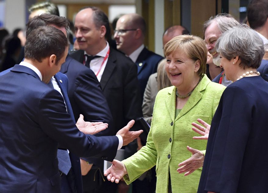 German Chancellor Angela Merkel, second right, speaks with French President Emmanuel Macron, left, and British Prime Minister Theresa May, right, during a round table meeting at an EU summit in Brussels on Thursday, June 22, 2017. European Union leaders are gathering for a two day summit to weigh measures in which to tackle terrorism and migration and to create closer defense ties. (AP Photo/Geert Vanden Wijngaert)