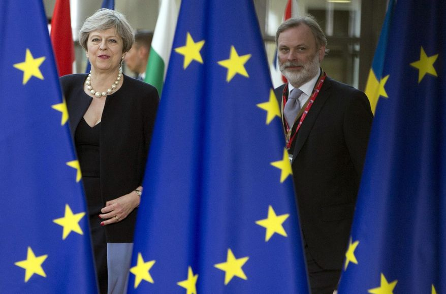 British Prime Minister Theresa May, left, and UK representative to the EU Tim Barrow arrive for an EU summit at the Europa building in Brussels on Thursday, June 22, 2017. European Union leaders are gathering for a two day summit to weigh measures to tackle terrorism and migration and to create closer defense ties. (AP Photo/Virginia Mayo)