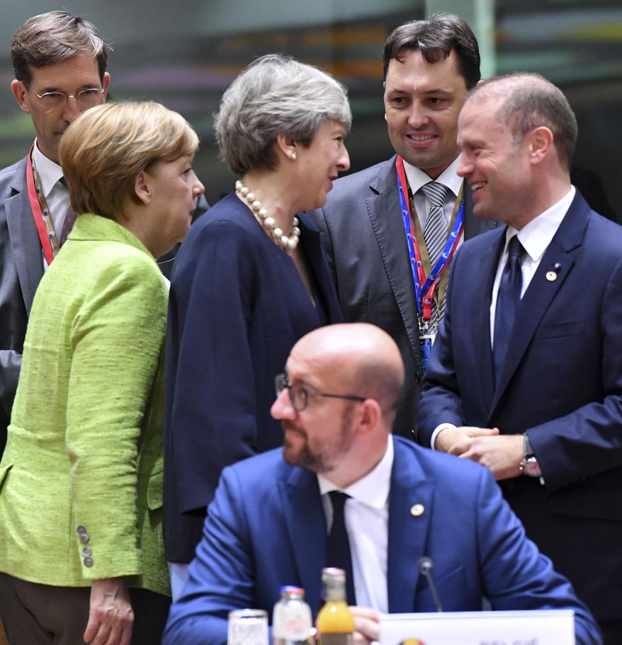 German Chancellor Angela Merkel, left, walks by as British Prime Minister Theresa May, center left, speaks with Malta's Prime Minister Joseph Muscat, right, during a round table meeting at an EU summit in Brussels on Thursday, June 22, 2017. European Union leaders are gathering for a two day summit to weigh measures in which to tackle terrorism and migration and to create closer defense ties. (AP Photo/Geert Vanden Wijngaert)