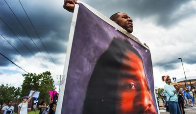 John Thompson, who said he was a close friend of Philando Castile, protests during a demonstration, Sunday, June 18, 2017, in St. Anthony, Minn. The protesters marched against the acquittal of Officer Jeronimo Yanez, was found not guilty of manslaughter for shooting Castile during a traffic stop. (Richard Tsong-Taatarii/Star Tribune via AP)