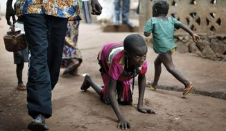 File--In this April 14, 2014 photo, Hamamatou Harouna, 10, crawls to the restroom on the grounds of the Catholic Church where she and hundreds of others found refuge in Carnot, Central African Republic. Human Rights Watch says people with disabilities in Central African Republic are at high risk during attacks and forced displacement, facing neglect in an ongoing humanitarian crisis. (AP Photo/Jerome Delay)