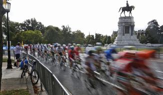 FILE - In this Sept. 27, 2015 file photo the peloton of the UCI Elite Men's Road World Championship passes by the statue of Confederate Gen. Robert E. Lee on Monument Avenue in Richmond, Va. Richmond Mayor Levar Stoney announced Thursday, June 22, 2017, the formation of a commission to help redefine the narrative of the statues on the avenue. (AP Photo/Steve Helber)