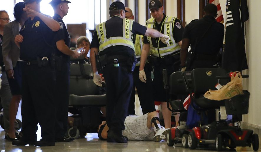 Capitol Police prepare to remove a man from a sit-in of Senate Majority Leader Mitch McConnell's office, as he and others protest proposed caps to Medicaid Thursday, June 22, 2017, on Capitol Hill in Washington. (AP Photo/Jacquelyn Martin)