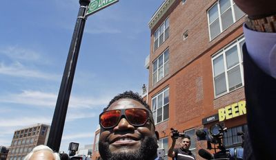 Retired Boston Red Sox designated hitter David Ortiz smiles as he shoots a selfie during a gathering where part of Yawkey Way was renamed David Ortiz Drive outside Fenway Park in Boston, Thursday, June 22, 2017. Ortiz's No. 34 will be retired in a ceremony prior to Friday night's game. (AP Photo/Charles Krupa)