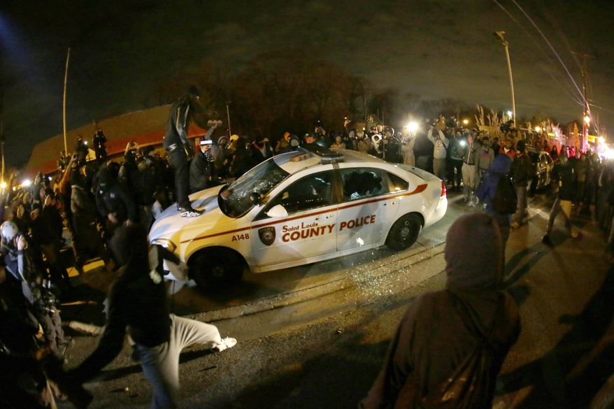 FILE - In this Nov. 24, 2014, file photo, a protester squirts lighter fluid on the police car as the car windows are shattered near the Ferguson Police Department after the announcement of the grand jury decision in Ferguson, Mo, deciding not to indict Ferguson police officer Darren Wilson in the death of Michael Brown, the unarmed, black 18-year-old whose fatal shooting sparked sometimes violent protests. Attorneys for the U.S. Department of Justice say Ferguson, Missouri, is making progress in the effort to end racial bias in police and court practices, but more transparency is needed. U.S. District Judge Catherine Perry on Thursday, June 22, 2017, heard an update on a consent agreement reached in 2016.(AP Photo/Charlie Riedel, File)