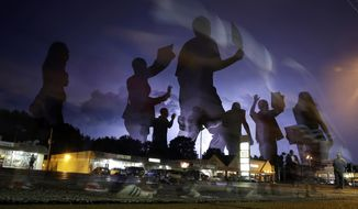 FILE - In this Aug. 20, 2014, file photo, protesters march in the street as lightning flashes in the distance in Ferguson, Mo., following the shooting of Michael Brown, an unarmed black 18-year old, in the St. Louis suburb on Aug. 9. Attorneys for the U.S. Department of Justice say Ferguson, Missouri, is making progress in the effort to end racial bias in police and court practices, but more transparency is needed. U.S. District Judge Catherine Perry on Thursday, June 22, 2017, heard an update on a consent agreement reached in 2016. (AP Photo/Jeff Roberson, File)